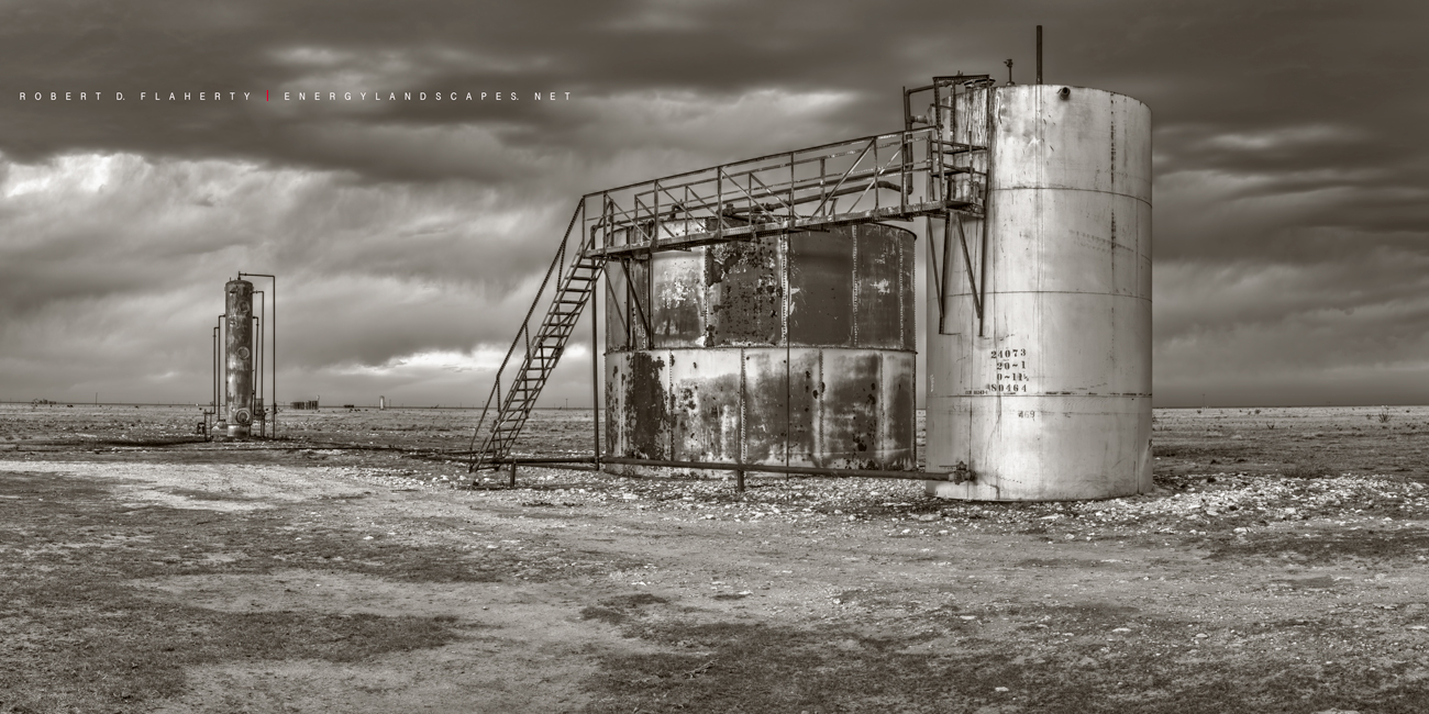Tanks At Bush Draw is a sepia toned black & white 2:1 panoramic print featuring the tanks and separator from the larger 3:1 panoramic...